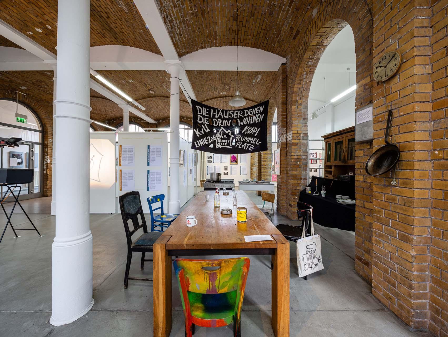 """Der Tisch in der Küche ist ein zentraler Ort des Zusammenlebens. In der Installation der Ausstellung """"Häuser besetzen sowieso"""" nimmt er daher auch den wichtigsten Platz ein. Foto: Giovanni Lo Curto"""